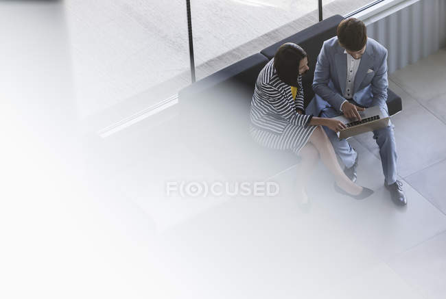 Empresario y empresaria trabajando, compartiendo portátil en el vestíbulo de la oficina - foto de stock