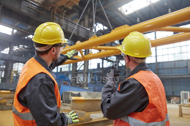 Male workers watching equipment being raised in factory — Stock Photo