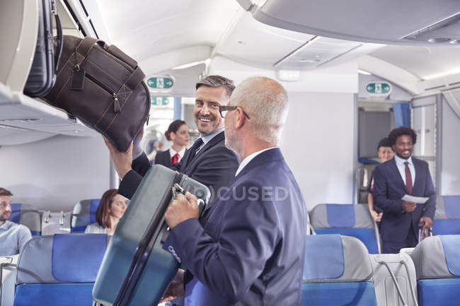 Empresarios cargar equipaje en el compartimiento del avión - foto de stock