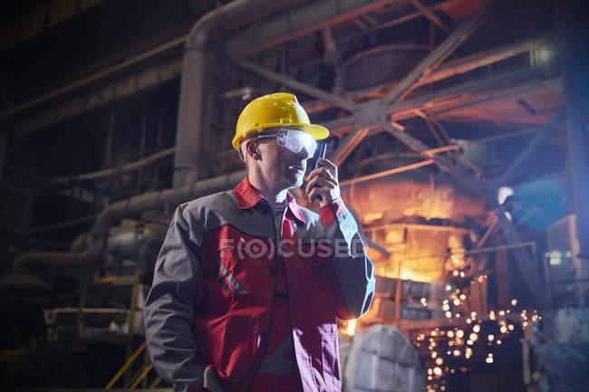 Stahlarbeiter im Gespräch mit Walkie-Talkie im Stahlwerk — Stockfoto