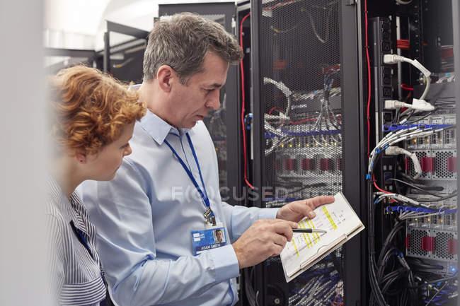 Это техников с буфером обмена, изучения группа в серверной комнате — стоковое фото