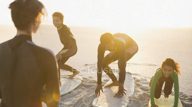 Father surfer teaching children surfing on surfboards on sunny summer beach — Stock Photo