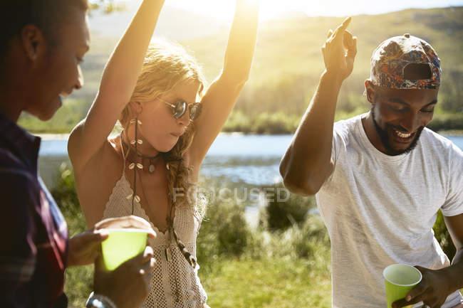 Verspielte junge Freunde tanzen an sonnigem Sommerufer — Stockfoto