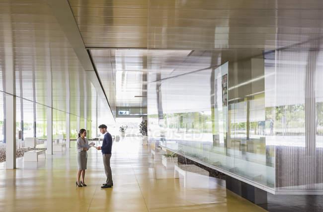 Empresário e empresária conversando no moderno corredor do lobby do escritório — Fotografia de Stock