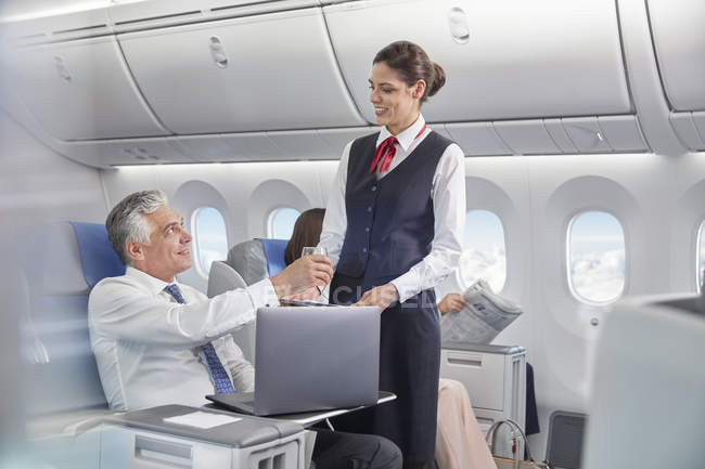 Flight attendant serving drink to businessman working at laptop on airplane — Stock Photo