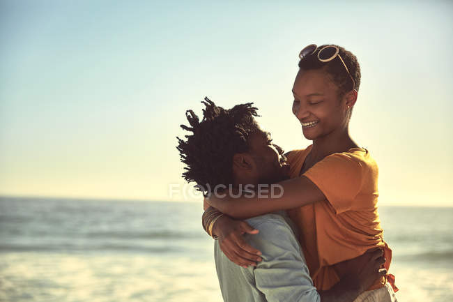 Affectionate young couple hugging on sunny summer beach — Stock Photo