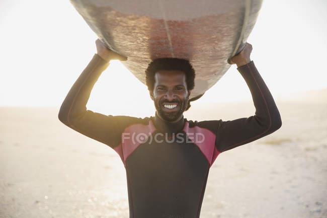 Портрет, улыбаясь, уверенно мужской серфер нося серфинг накладные расходы на солнечный летний пляж — стоковое фото