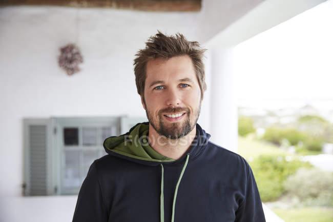 Porträt lächelnder brünetter Mann mit Kapuzenpulli auf der Terrasse — Stockfoto