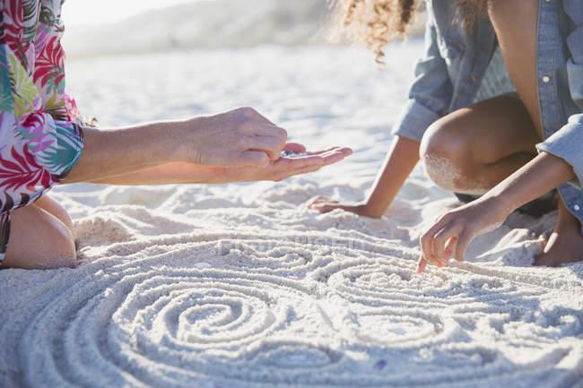 Мати і дочка розміщення черепашки по спіралі в піску на пляжі сонячних літніх — стокове фото
