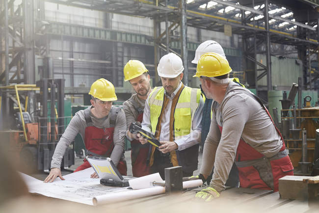 Male foreman, engineers and workers with digital tablet meeting in factory — Stock Photo
