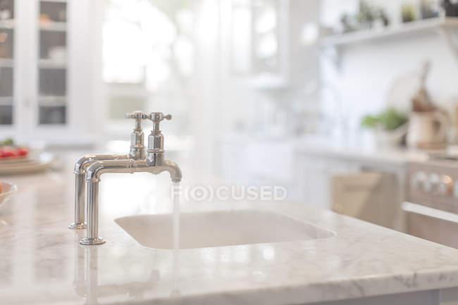 Eau qui coule du robinet à l'évier de cuisine — Photo de stock