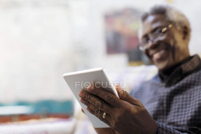 Homme senior souriant, à l'aide de tablette numérique — Photo de stock