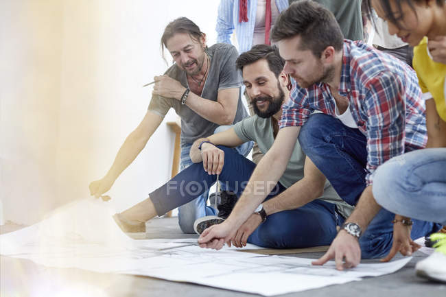 Artists discussing sketches on floor in art class studio — Stock Photo