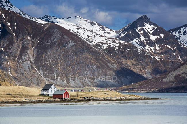 Віддалених будинків по фіорд нижче скелястій гори, Flakstadpollen, Лофотені, Норвегія — стокове фото