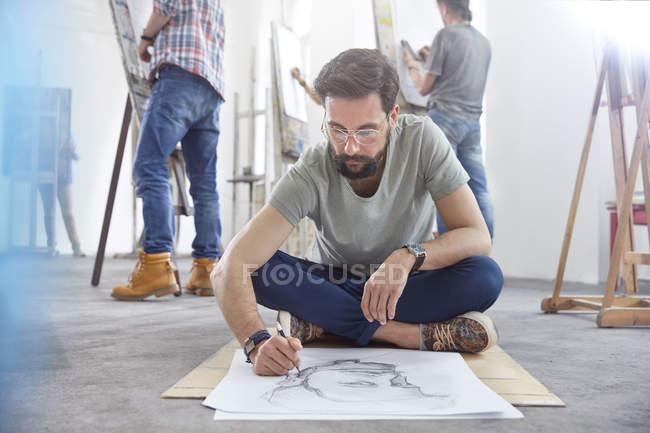 Male artist sitting cross-legged sketching on floor in art class studio — Stock Photo