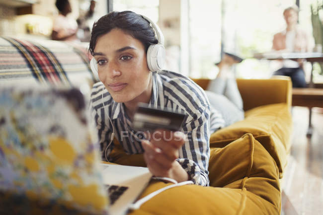 Young woman with credit card and headphones online shopping at laptop on living room sofa — Stockfoto