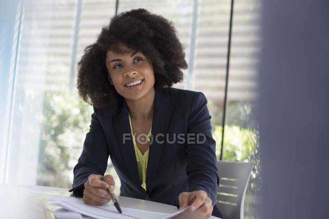 Smiling businesswoman explaining paperwork in meeting — Stock Photo