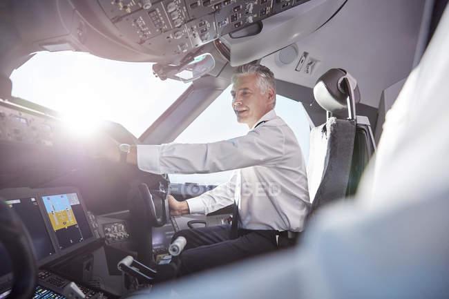 Smiling male pilot in airplane cockpit - foto de stock