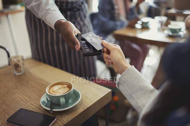 Клієнт кредитною карткою оплати працівника з безконтактних платежів в кафе — стокове фото