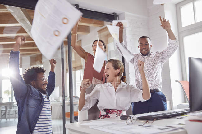 Exuberant business people celebrating, throwing paperwork overhead in office — Stock Photo