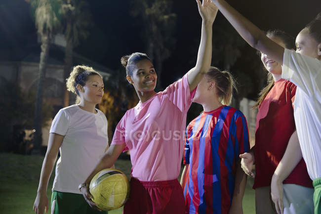 Confident young female soccer teammates high-fiving on field at night — Stock Photo