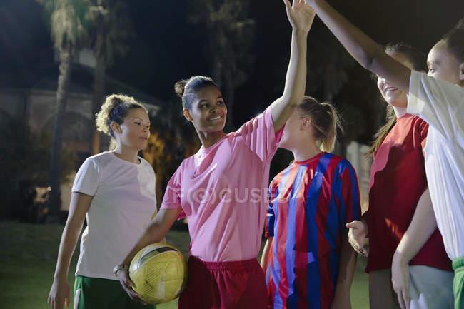 Уверенно молодых женский футбол высокого fiving команде на поле ночью — стоковое фото