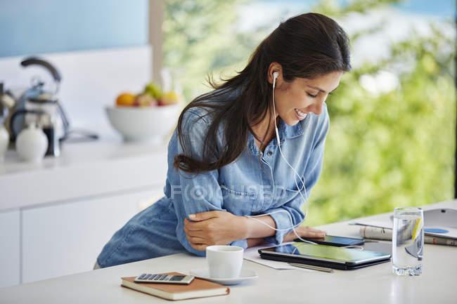 Femme souriante, écouter de la musique avec des écouteurs et lecteur mp3 dans la cuisine — Photo de stock
