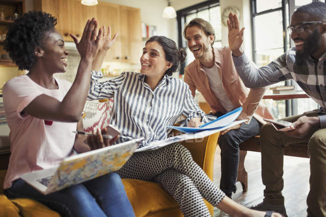 Creative business people high-fiving in meeting — Stock Photo