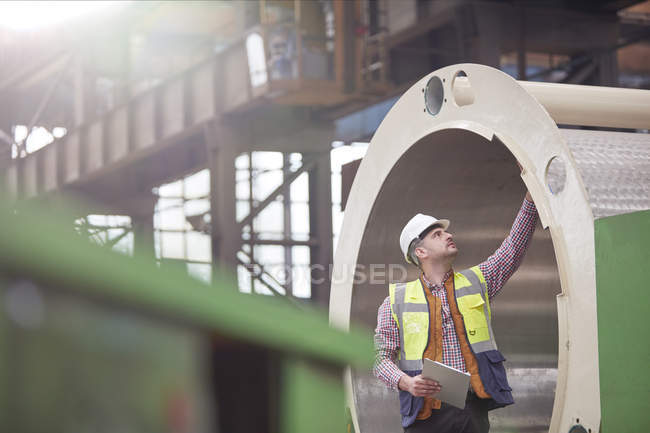 Мужчины инженер с буфером обмена, изучения стальных труб на заводе — стоковое фото