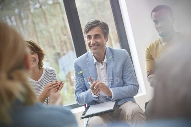 Smiling man clapping in group therapy session — Stock Photo