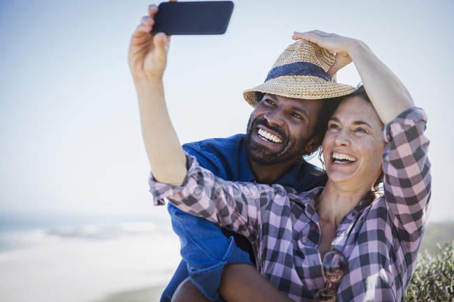 Игривый, улыбаясь многоэтнического пара принимая selfie с камеры телефона на солнечный летний пляж — стоковое фото