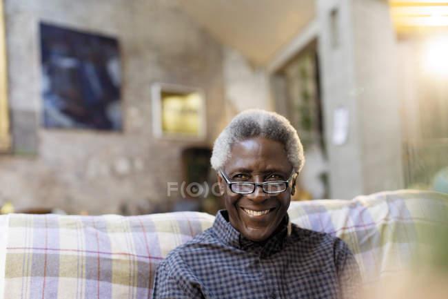 Porträt lächelnder, selbstbewusster Senior auf dem Sofa — Stockfoto