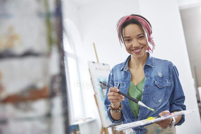 Retrato sonriente mujer artista con pincel y paleta, pintura en el estudio de la clase de arte - foto de stock