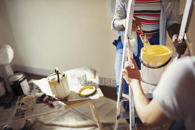 Жінки з жовтою фарбою живопису вітальні — стокове фото