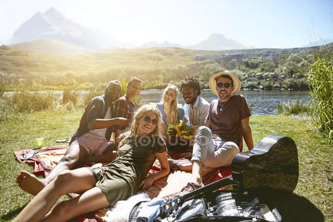 Porträt lächelnde junge Freunde, die am sonnigen Sommerufer picknicken — Stockfoto