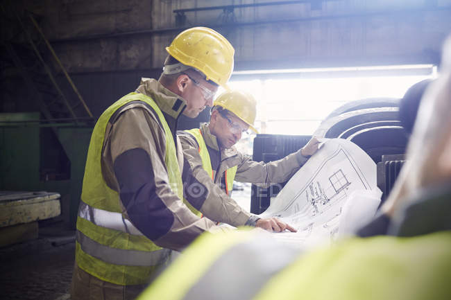 Engineer and steelworker examining blueprints in steel mill — Stock Photo