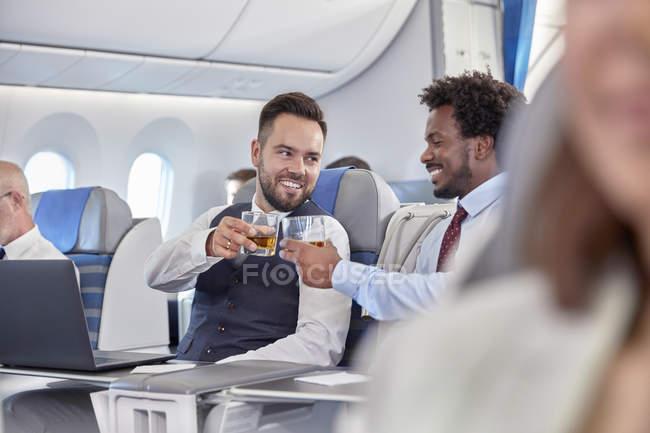 Empresários, brindando copos de uísque no avião de primeira classe — Fotografia de Stock