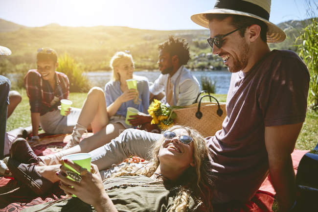 Young friends relaxing, enjoying picnic at sunny summer riverside — Stock Photo
