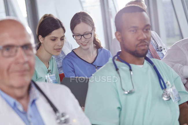 Female nurses talking in conference audience — Stock Photo