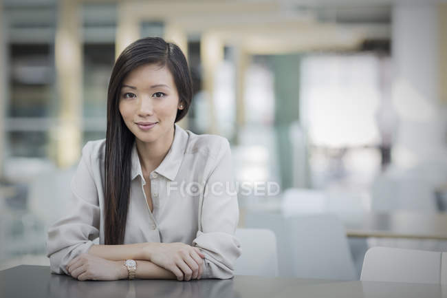 Portrait confident businesswoman at table at modern office — Stock Photo