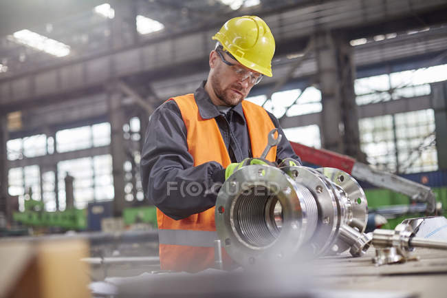 Male worker assembling steel part in factory — Stock Photo