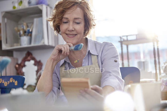 Smiling mature female artist painting wood in art class workshop — Stock Photo