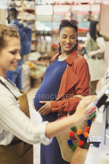 Cashier helping pregnant female shopper at grocery store cash register — Stock Photo