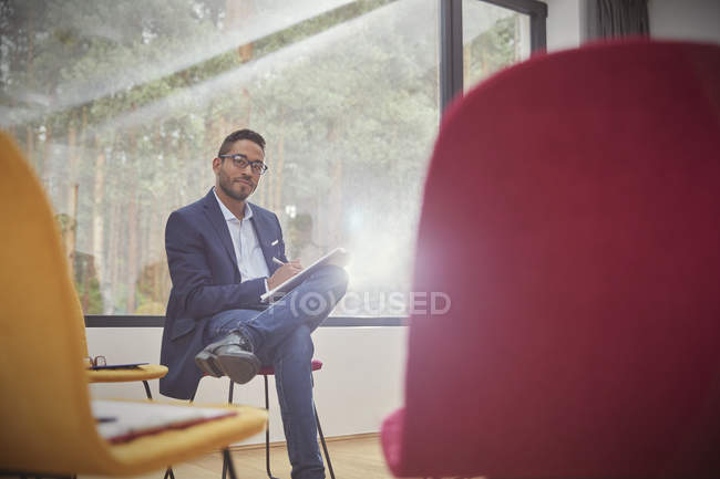 Portrait confident businessman writing on clipboard in office — Stock Photo