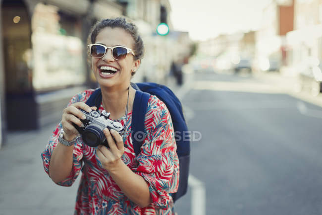 Portrait laughing, enthusiastic young female tourist in sunglasses photographing with camera on urban street — Stock Photo