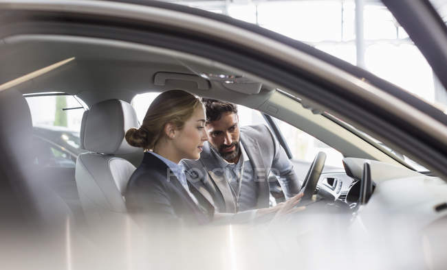 Car salesman showing new car to woman in driver?s seat at car dealership — Stock Photo