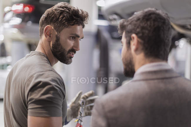 Auto mechanic talking, explaining to customer in auto repair shop — Stock Photo