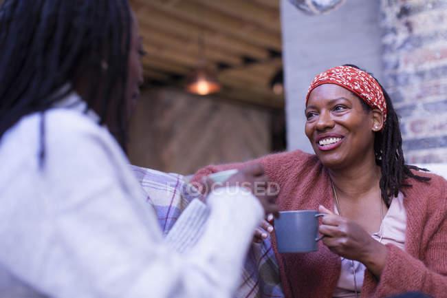 Lächelnde Freundinnen reden und trinken Kaffee — Stockfoto