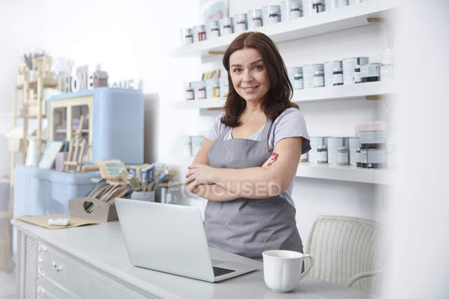 Portrait confident, smiling art shop business owner standing at counter — Stock Photo