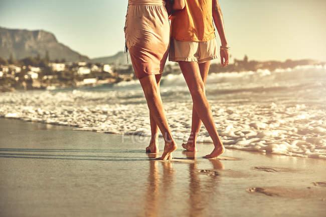 Босоніж молодих жінок, що йдуть на пляжі сонячних літніх океану — стокове фото